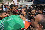 Mourners carry the body of Palestinian Nidal Shatat, 29, who was shot dead by Israeli forces during clashes with Israeli troops in tents protest where Palestinians demand the right to return to their homeland at the Israel-Gaza border, mourn over his body during his funeral in the center of Gaza strip, on March 23, 2019. Photo by Ashraf Amra