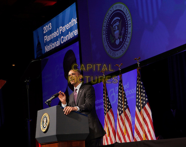 Barack Obama.United States President Barack Obama speaking at the Planned Parenthood Gala at the Washington Marriott Wardman Park Hotel in Washington, DC, USA, April 26, 2013..half length podium American flags  suit tie speaking  purple politics hand microphone side .CAP/ADM/CNP/CK.©Chris Kleponis/AdMedia/Capital Pictures