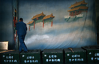 Opera012 20030207 SHANXI, CHINA: A stage hand looks as if he is walking on clouds in front of a backdrop portraying the heavenly gates before a performance at a rural village in Shanxi Province, China 07 February 2003. Many of the troupe's performances deals with immortals who reside in the heavens, thus creating the need for such a backdrop.