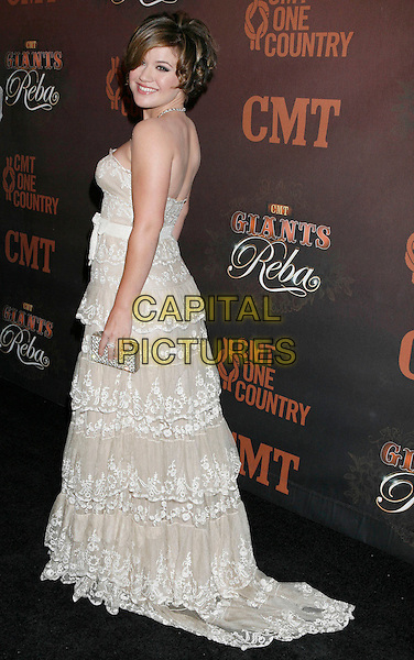 """KELLY CLARKSON.Arrivals at """"CMT Giants"""" Honoring Reba McEntire held at the Kodak Theatre, Hollywood, LA, California, USA,.26 October 2006..full length looking back over shoulder white lace ruffle layered dress strapless.Ref: ADM/RE.www.capitalpictures.com.sales@capitalpictures.com.©Russ Elliot/AdMedia/Capital Pictures."""
