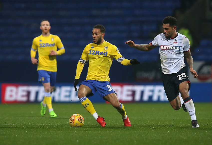 Leeds United's Lewis Baker and Bolton Wanderers' Josh Magennis<br /> <br /> Photographer Stephen White/CameraSport<br /> <br /> The EFL Sky Bet Championship - Bolton Wanderers v Leeds United - Saturday 15th December 2018 - University of Bolton Stadium - Bolton<br /> <br /> World Copyright © 2018 CameraSport. All rights reserved. 43 Linden Ave. Countesthorpe. Leicester. England. LE8 5PG - Tel: +44 (0) 116 277 4147 - admin@camerasport.com - www.camerasport.com