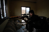 Photographer: Rick Findler..06.10.12 A sniper belonging to the Free Syrian Army sits patiently in an abandoned fifth-story bedroom in the city of Aleppo, Syria.