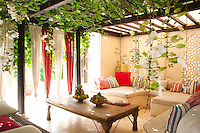 This secluded seating area on the roof terrace is shaded by a lush pergola and simple curtains