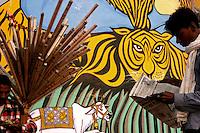 30.11.2008 Varanasi(Uttar Pradesh)<br /> <br /> A seller of flutes eating near a man reading newspaper in the main ghat.<br /> <br /> Un vendeur de flûtes en train de manger pres d'un homme lisant le journal sur le ghat principal.