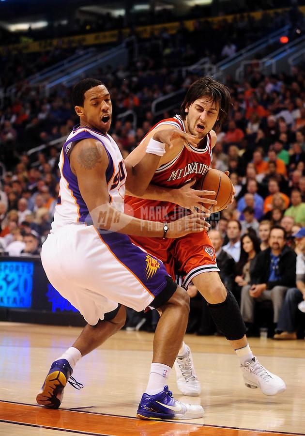 Jan. 11, 2010; Phoenix, AZ, USA; Milwaukee Bucks center (6) Andrew Bogut drives to the basket past Phoenix Suns center (8) Channing Frye in the first half at the US Airways Center. Mandatory Credit: Mark J. Rebilas-