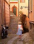 A woman wearing a straw hat walks down a cobble stone path in Blevio, a town on Lake Como, Italy