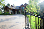 the gated entrance, circular entry, and covered entry drive, or porte cochere, of a large, lodge like, estate property in the late afteroon summer sunshine with sparkly lens flare for effect