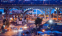 "The illuminated artwork ""The ""H"" in Harlem"" is seen hanging under the 125th Street viaduct in Harlem in New York on Tuesday, July 1, 2014. The aluminum truss structure with 30 LED fixtures attached and illuminated by plasma lighting was designed by lighting designer and artist Bentley Meeker. The sculpture will remain on view until September 25. (© Richard B. Levine)"