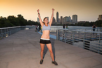 Female runner raises hands in training victory on The Boardwalk Trail along Lady Bird Lake with the magestic Austin Skyline background.