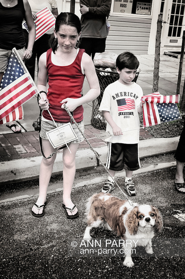 Merrick, New York, U.S. - May 30, 2011 - Freckled girl with dog, and young boy at Memorial Day Parade, Merrick, New York, USA, on May 30, 2011. Tinted and textured noise added for vintage effect.