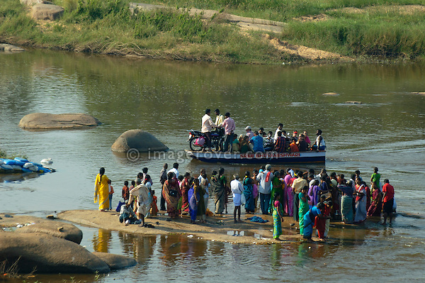 Local indian people crossing the Tungabhadra River with a small ferry. India, Karnataka, Hampi.