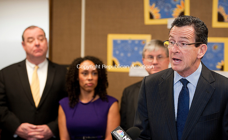 WATERBURY, CT-011614JS02- Governor Dannel P. Malloy talks about the recently signed contract for in-home child care workers during a news conferenceThursday in the Children's Room at the Silas Bronson Library in Waterbury. Standing behind Gov. Malloy is Waterbury Mayor Neil M. O'Leary, Myra Jones-Taylor , Executive Director for the State Office of Early Childhood and Emmett McSweeney, Director of the Silas Bronson Library. <br /> Jim Shannon Republican-American