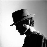 Silhouetted face of a man in a fedora hat