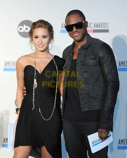 DEMI LOVATO & TAIO CRUZ .at The 2010 American Music Award Nomination Announcements held at The JW Marriott Los Angeles at L.A. Live in Los Angeles, California, USA, .October 12th 2010..half length dress black one shoulder sunglasses jacket denim leather sleeves arm around  necklace .CAP/RKE/DVS.©DVS/RockinExposures/Capital Pictures.