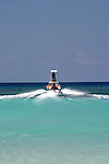 A dive boat cruise through a break in the coral reef off West Bay on the island of Roatan, Honduras.