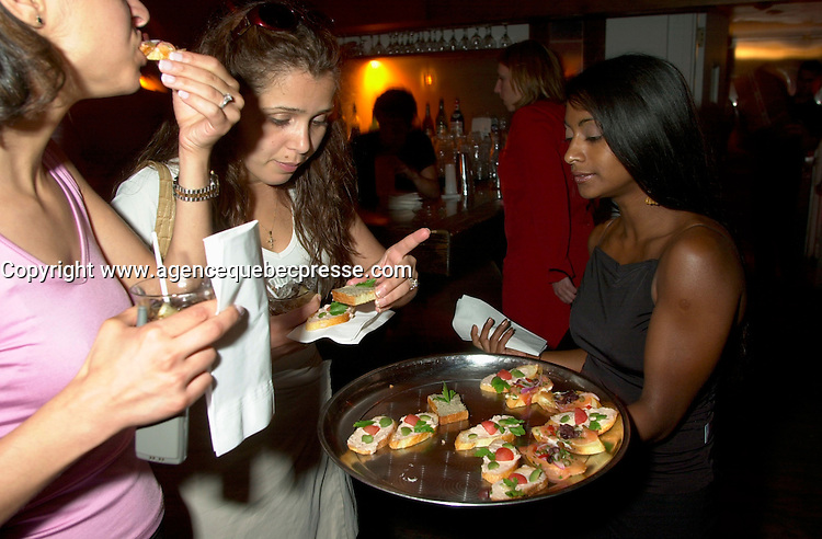 June 4 2002, Montreal, Quebec, Canada<br /> <br />  Unidentified partygoers tast appetizers from GLOBE Restaurant , served by waitress Marie Soleil Lavoie (R) during  a party at ilume club, in Montreal, JUne 4, 2002 after the opening of McKinney's play ; Fully Committed.<br /> <br /> Formelly of The Kids In The Hall Canadian TV show, McKinney now based in New York, plays in movies and TV series such as DICE, Brain Candy, ... as well as doing comedy and theater.<br /> <br /> Mandatory Credit: Photo by Pierre Roussel- Images Distribution. (&copy;) Copyright 2002 by Pierre Roussel <br /> <br /> NOTE :l Nikon D-1 jpeg opened with Qimage icc profile, saved in Adobe 1998 RGB.