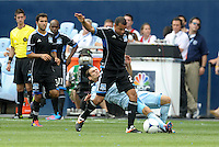 San Jose defender Jason Hernandez (21)  tackled by Kansas City midfielder Graham Zusi... Sporting Kansas City defeated San Jose Earthquakes 2-1 at LIVESTRONG Sporting Park, Kansas City, Kansas.