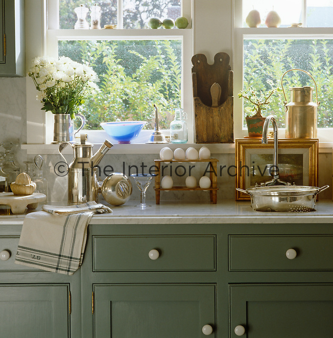 Detail of a green Shaker-style kitchen with a white marble work surface