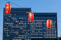 Red and white festival lanterns hang in front of office buildings during the celebrations of the Obon summer festival in Hibiya Park, Tokyo, Japan. Friday August 22nd 2014