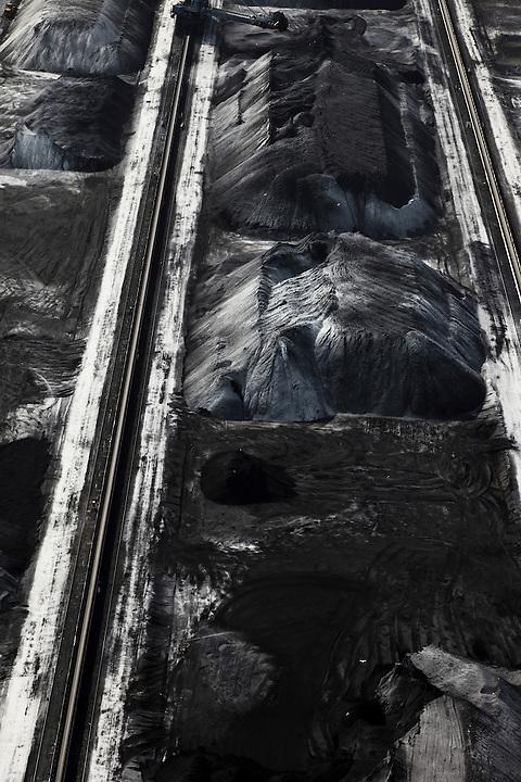 Nederland, Zuid-Holland, Europoort,  23-05-2011; Ertsoverslagbedrijf Europoort C.V. (EECV) aan de Dintelhaven, met op het tweede plan Calankanaal en de Nieuwe Waterweg.Steenkoolopslag..Coal storage at the Ore Transfer Company Europoort C.V. (EECV) at  Dintelhaven (Dintel harbour) in the Port of Rotterdam..luchtfoto (toeslag), aerial photo (additional fee required).copyright foto/photo Siebe Swart