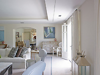 Light floods into the living room from large French windows flung open to the garden beyond