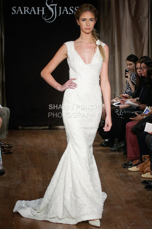"""Model walks runway in a Celine Bridal dress - sequin beaded gown with a deep V-neck and keyhole back, by Sarah Jassir, for the Sarah Jassir Spring 2013 """"La Reve: The Dream"""" collection, during Bridal Fashion Week New York."""