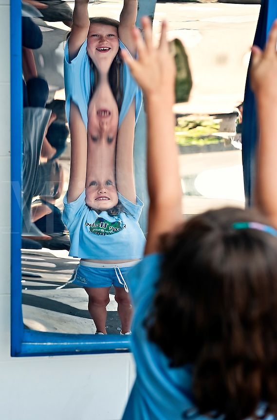 Young girl enjoys the effects of a curved distortion mirror.