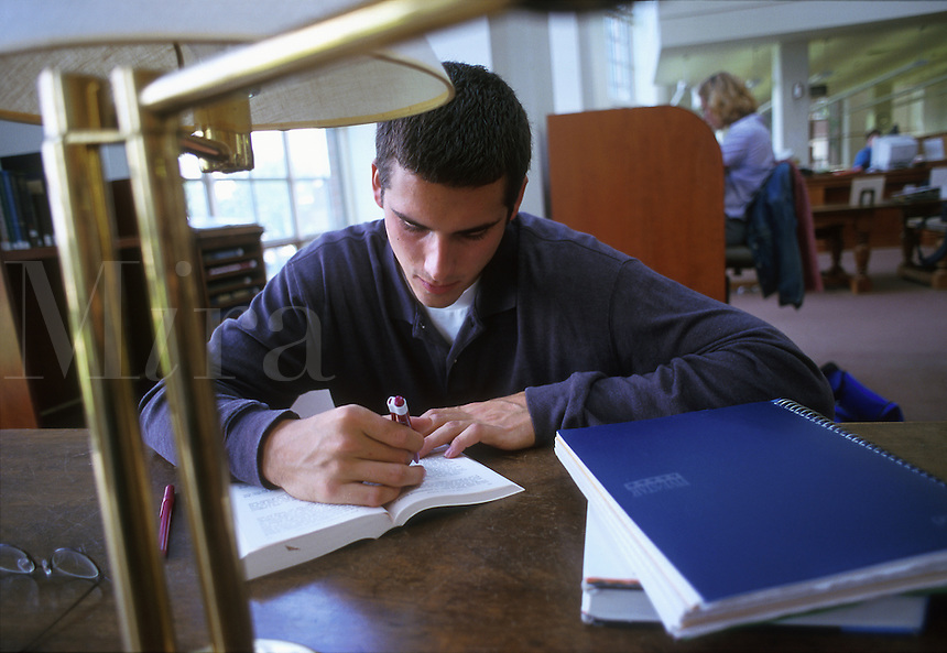 A male college student studying in the library.