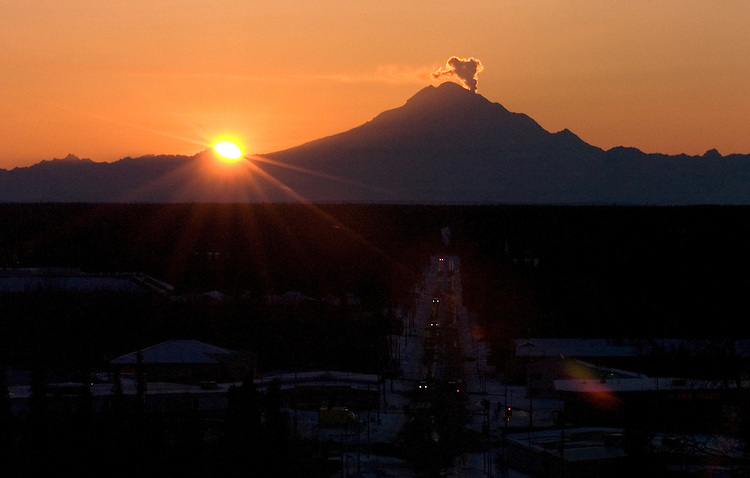 A steam plume rises as the sun sets behind Mount Redoubt volcano, about 50 miles across Cook Inlet from Soldotna, Alaska, at the beginning of an eruptive period in 2009.