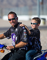 Apr 12, 2015; Las Vegas, NV, USA; NHRA funny car driver Jack Beckman riding a scooter with his son during the Summitracing.com Nationals at The Strip at Las Vegas Motor Speedway. Mandatory Credit: Mark J. Rebilas-