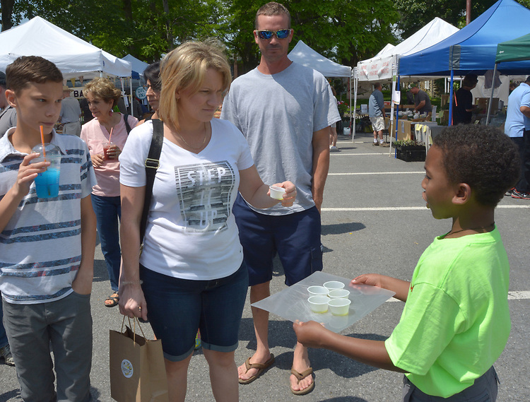 The youngest entreprenour, of the Seasoned Delicious concession, Amitai Lewis) seen working the crowd, at the Saugerties Farmer's Market on Main Street in the Village of Saugerties, NY, on Saturday, June 10, 2017. Photo by Jim Peppler. Copyright/Jim Peppler-2017.