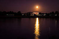 A brilliant Full Harvest Moon shines down and casts a bright reflection on the waters of San Leandro Bay at the MLK Regional Shoreline in Oakland, California.