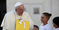 Papa Francesco riceve un dono da alcuni bambini al suo suo arrivo all'udienza generale del mercoledi' in Piazza San Pietro, Citta' del Vaticano, 11 settembre, 2019.<br /> Pope Francis holds a present he was offered by children, on the popemobile, as he arrives for his weekly general audience, at the Vatican on September 9, 2019.<br /> UPDATE IMAGES PRESS/Isabella Bonotto<br /> <br /> STRICTLY ONLY FOR EDITORIAL USE