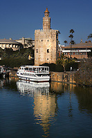 General view of Torre del Oro (Tower of Gold) and River Guadalquivir, Seville, Spain, pictured on December 30, 2006, in the afternoon. The tower, first half of the 13th, century, is dodecagonal in shape and divided into three levels. The circular top level was added in 1760. It served as an observation post at the entrance to the port on the Guadalquivir River during the conquest of Americas. Today it houses the city's Naval Museum. A pleasure boat is moored on the river next to the Tower. Picture by Manuel Cohen.