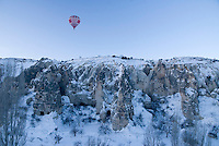Goreme, Nevsehir, Cappadocia, Turkey. a balloon takes off over the open air museum.  With a hot air balloon of Kapadokya Balloons we glide over the valleys of Goreme National Park. A fresh pack of snow has turned the winter landscape into an even bigger fairy tale. Photo by Frits Meyst / MeystPhoto.com