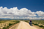 Man and woman riding motorcycle through dry puna, Andes, western Bolivia