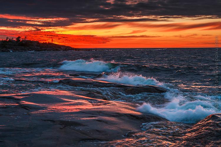 Brytande kulingvågor mor klippor vid havet på Arholma vid solnedgången.