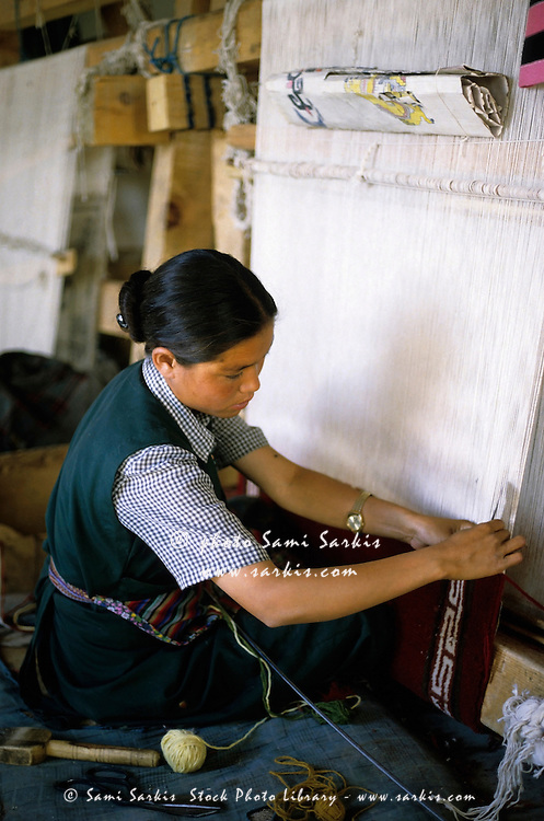 Woman weaving a carpet on a loom at a Tibetan Refugee Camp, Ladakh, Leh, India.