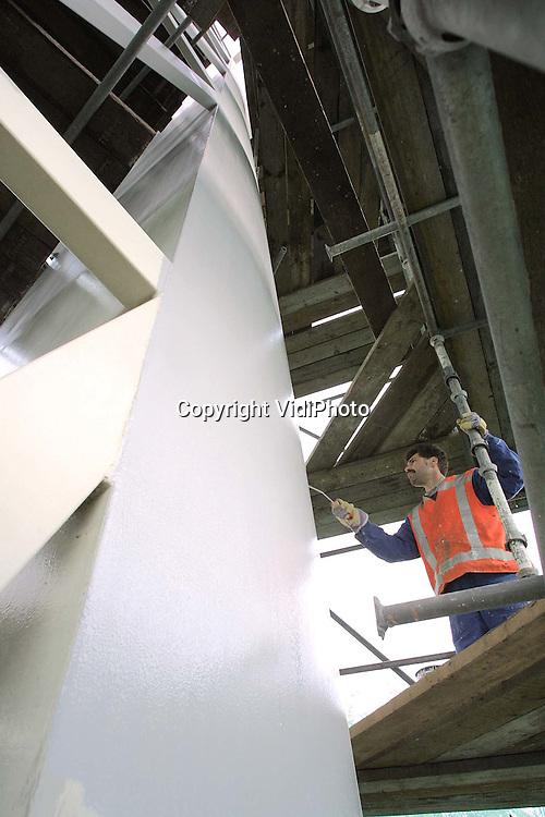Foto: VidiPhoto..ARNHEM - Schilders van Hertel Services uit Schoonebeek werken tijdens een droog moment aan de binnenzijde van het ingepakte 18,5 meter hoge 'Observatorium' langs de Pleyroute in Arnhem. Het stalen kunstwerk van de kunstenaar Jos Kokke krijgt op dit moment een flinke opknapbeurt. De werkzaamheden lopen echter vertraging op door het natte weer. Daarom wordt er een zogenoemde winterkwaliteit-verf gebruikt. Het is sinds 1988 de tweede keer dat het opvallende kunstwerk een schilderbeurt krijgt.