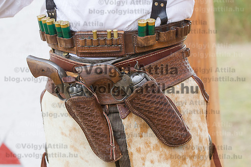 Participant wearing period dress carries his pistols during the Cowboy Action Shooting European Championship in Dabas, Hungary on August 11, 2012. ATTILA VOLGYI