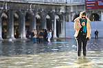 Tourist with boots on flooded St Mark's square during an acqua alta (high-water). The Acqua Alta, a convergence of high tides and a strong sirocco, reached 125 centimetres in Venice, on November 20, 2013.  <br /> <br /> &copy; Pierre Teyssot