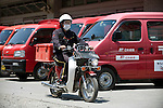 Postman Yoshinori Shoji sets off to deliver letters to an evacuation shelter at the KadonowakiJunior HighSchool in Ishinomaki, Miyagi Prefecture, Japan on Tuesday 24 May 2011. Some 350 motorcycles and 160 four-wheeled vehicles were destroyed following the March 11 quake and tsunamis..Photographer: Robert Gilhooly