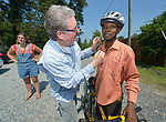 Casmil Ngundakumana, a refugee from Rwanda, gets his helmet adjusted before riding a bike in Durham, North Carolina, on July 22, 2017. He&rsquo;s helped by Greg Garneau, a volunteer who coordinates the refugee bike program for the Durham Bicycle Co-op.<br /> <br /> Ngundakumana was resettled in Durham by Church World Service, which resettles refugees in North Carolina and throughout the United States.<br /> <br /> Photo by Paul Jeffrey for Church World Service.
