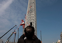 A Japanese office worker or slaryman uses a mobile phone to take a photo of the Tokyo Sky Tree under construction. In this image this new telecommunication tower stands at 398 metres and when finished will measure 634 metres from top to bottom making it the tallest structure in East Asia. Oshiage, Tokyo, Japan June 21st 2010