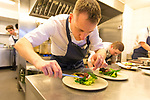 Chef Stephen Toman, head chef and owner of OX Restaurant, plating food in the open kitchen at OX Restaurant in Belfast, Northern Ireland