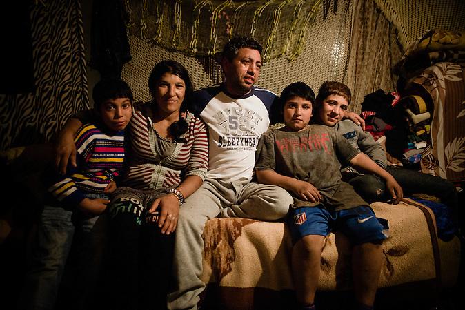"""Unter der Gazelabrücke in Belgrad steht die Hütte der Roma-Familie Galasovic/Musinovic. Das winzige windschiefe Gebäude dienst der 5-köpfigen Familie als Zuhause. Den Strom zapfen sie illegal ab, das Wasser sprudelt aus einer defekten Leitung im Garten. Durch das Projekt """"Belgrad am Wasser ist das Haus vom Abriss bedroht. Vater sufet Musinovic sagt: """"Wenn die Bagger kommen, dann bleibe ich hier im Haus zurück."""""""