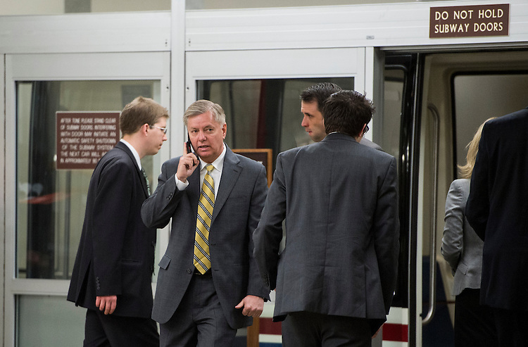 UNITED STATES - MARCH 12: Sen. Lindsey Graham, R-S.C., talks on his cell phone as he arrives in the Capitol for the Senate Republicans' policy lunch on Tuesday, March 2013. (Photo By Bill Clark/CQ Roll Call)