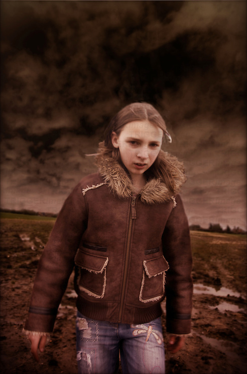 A young girl wearing a leather jacket outdoors under stormy clouds