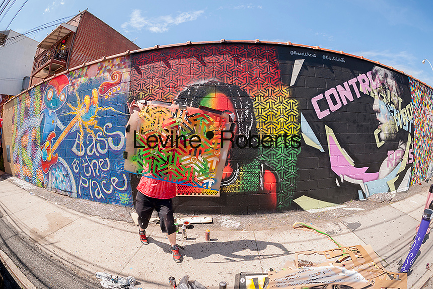 Street artist Eyez displays his stencil at the Welling Court Mural Project in the Astoria neighborhood of Queens in New York on Saturday, June 13, 2015. The annual neighborhood event decorates walls in this industrial part of Astoria. The project is crowd-funded and emerging street artists work side by side with established stars.  (© Richard B. Levine)