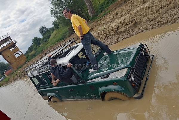 Standing on the bonnet and awaiting recovery for a Land Rover Defender stuck in a puddle while off roading in Bining, France. --- No releases available. Automotive trademarks are the property of the trademark holder, authorization may be needed for some uses.